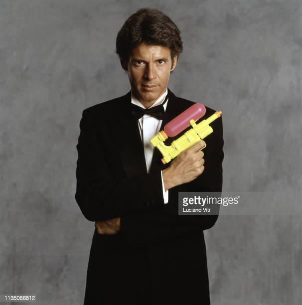 Italian singersongwriter Claudio Baglioni posing like 007 with a toy gun Rome Italy 1993