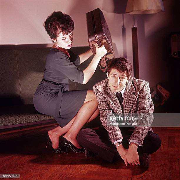 Italian singersongwriter comedy writer director and actor Giorgio Gaber sitting on the floor at home and his partner and Italian singer actress and...