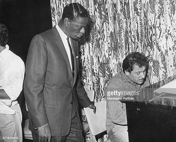 Italian singersongwriter Domenico Modugno playing piano beside American singer and pianist Nat King Cole 1950s