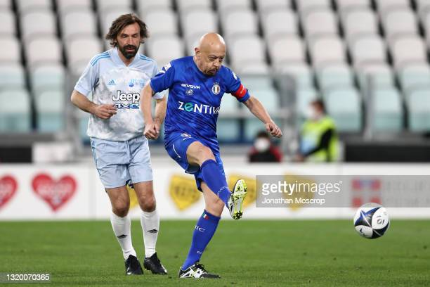 Italian Singer-Songwriter Enrico Ruggeri plays the ball as Andrea Pirlo, head coach of Juventus, looks on during the 30th 'Partita Del Cuore' charity...