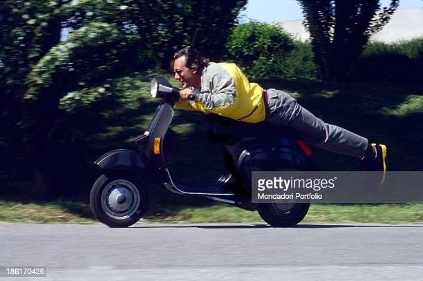 Italian singersongwriter Enzo Jannacci leaning on the saddle of a Vespa scooter Italy 1980