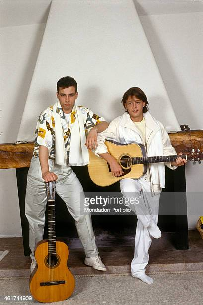 Italian singersongwriter Eros Ramazzotti leaning on a guitar posing in front of a fireplace with Mexican singer Luis Miguel Italy 1985