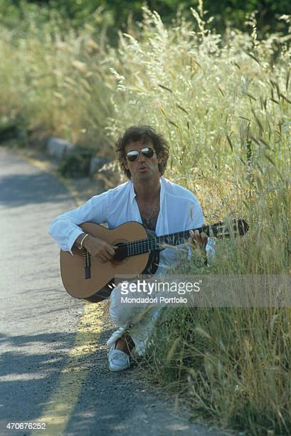 Italian singersongwriter Franco Califano playing guitar on the roadside wearing a pair of sunglasses 1981