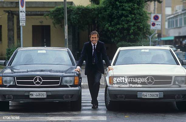 Italian singersongwriter Franco Califano posing leaned on the bonnet of two Mercedes cars Italy 1988