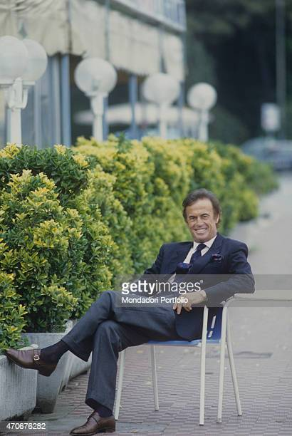 Italian singersongwriter Franco Califano posing seated on a chair wearing a suit Italy 1988