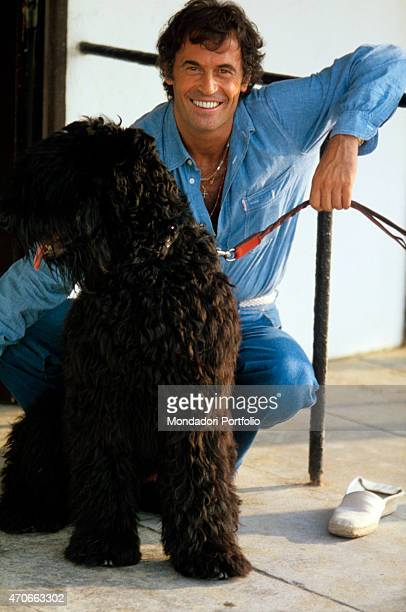 Italian singersongwriter Franco Califano posing smiling beside a dog 1978
