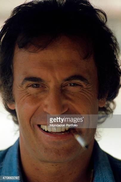 Italian singersongwriter Franco Califano posing smiling with a cigarette holder in his mouth 1978