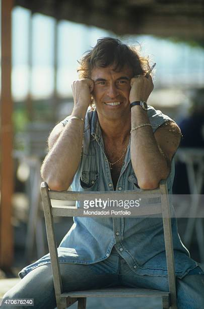 Italian singersongwriter Franco Califano sitting on a chair holding a cigarette 1981