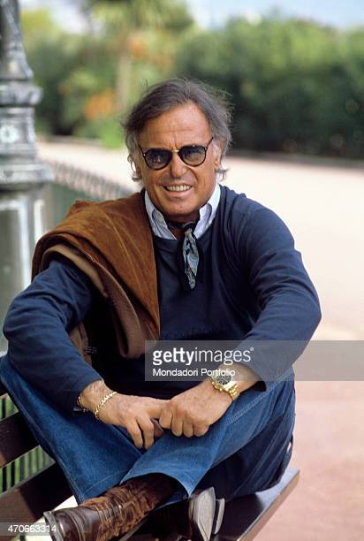 Italian singersongwriter Franco Califano smiling seated on a bench Monaco 1994