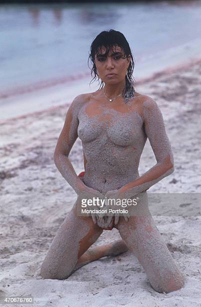 Italian singersongwriter Loredana Bert covered in sand posing topless kneeling on the beach 1988