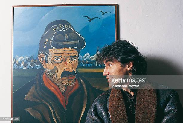 'Italian singersongwriter Luciano Ligabue posing beside a work by the painter bearing his same 'Ligabue con il casco da motociclista' Photocall...