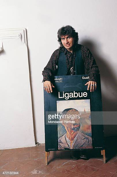 'Italian singersongwriter Luciano Ligabue posing resting his arms on the advertising poster dedicated to the painter Ligabue in a photocall shooted...