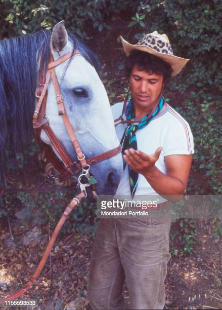 Italian singersongwriter Lucio Battisti caressing his horse Battisti is going for a ride from Milan to Rome with his friend Mogol Italy 1970