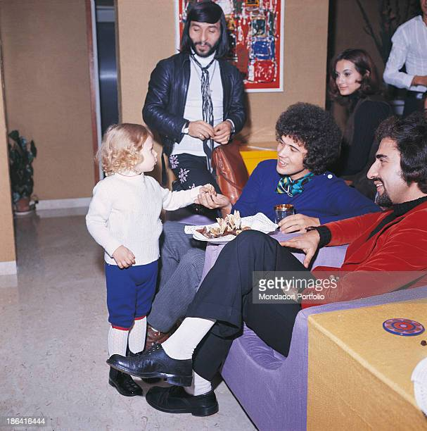 Italian singersongwriter Lucio Battisti looking smiling at a child in company of some friends among them Italian musician and drummer of band Equipe...