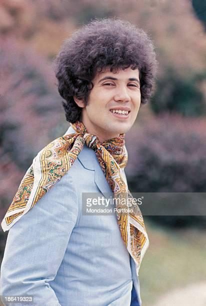 Italian singersongwriter Lucio Battisti posing smiling with a neckerchief around his neck 1973