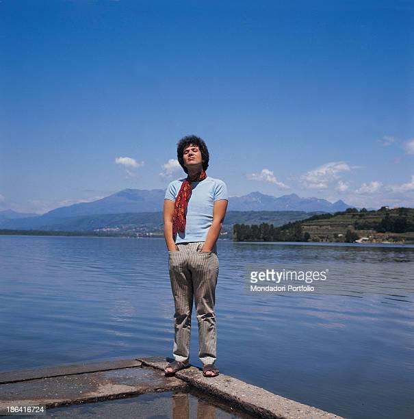 Italian singersongwriter Lucio Battisti standing on a concrete pier overlooking a lake Italy 1969