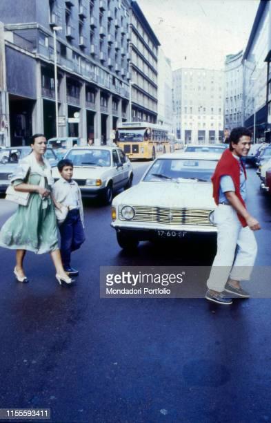 Italian singersongwriter Lucio Battisti walking along the street with his family Milan 1982