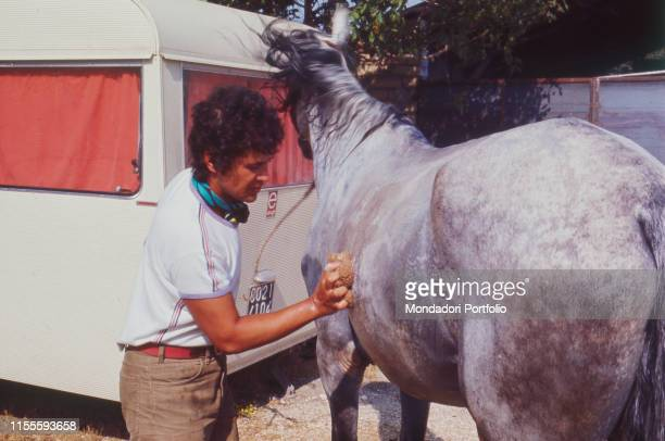 Italian singersongwriter Lucio Battisti washing his horse Battisti is going for a ride from Milan to Rome with his friend Mogol Italy 1970