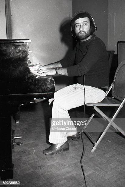 Italian singersongwriter Lucio Dalla plays the piano and records a song in his studio Rome 1971