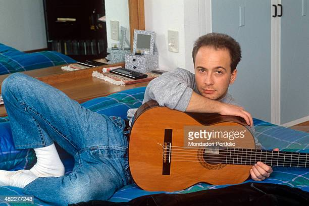 Italian singersongwriter Marco Masini posing on the bed with a guitar in his hands 1990