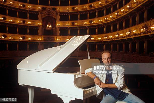 Italian singersongwriter Marco Masini posing sitting on the stool leaning on the piano before performing at the Teatro Comunale Ponchielli of Cremona...