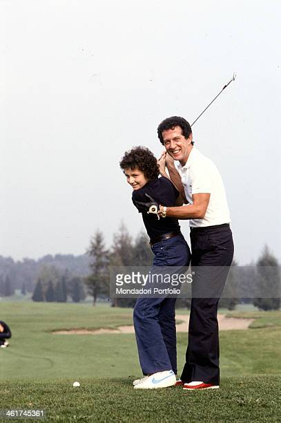 Italian singersongwriter Memo Remigi and his son Stefano playing golf 1981