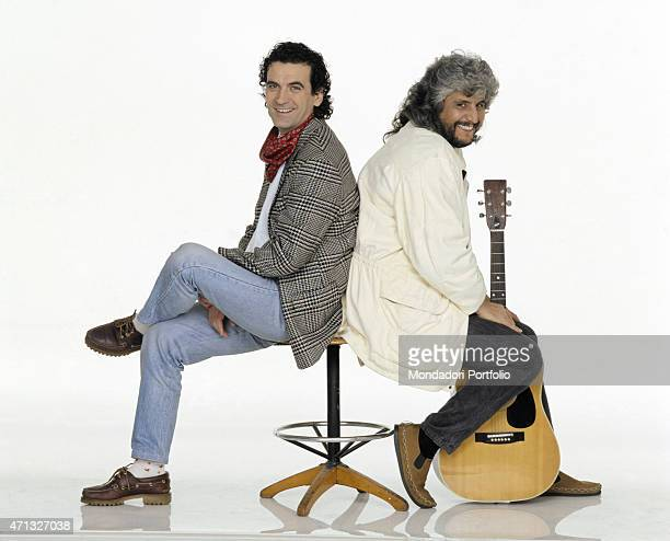 Italian singersongwriter Pino Daniele smiling with his guitar beside Italian actor and director Massimo Troisi 1991