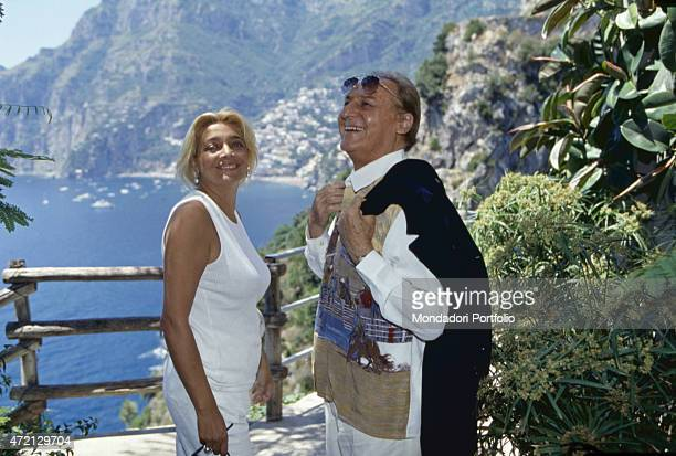 Italian singersongwriter radio host and showman Renzo Arbore smiling with italian TV presenter and actress Mara Venier in front of the gulf of...