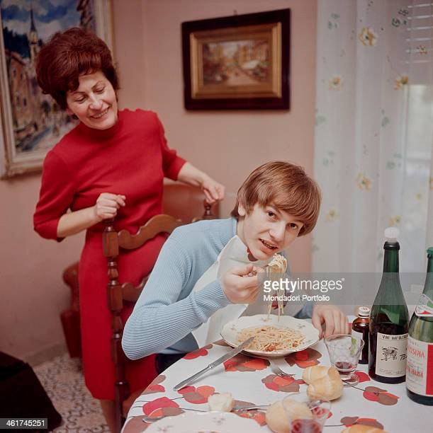 Italian singer-songwriter Ron eating the spaghettis cooked by his mother who's looking at him. Italy, 1970