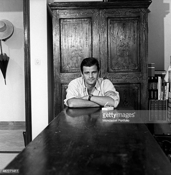 Italian singer-songwriter Sergio Endrigo sitting in front of a table at home in via Seneca 66. Rome, 1964
