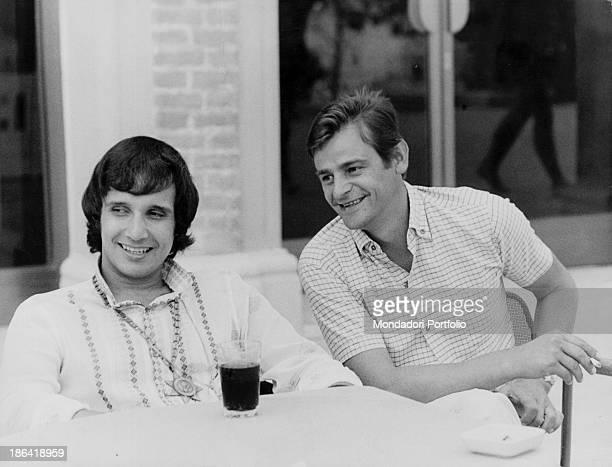 Italian singersongwriter Sergio Endrigo smiling and smoking a cigarette sitting beside Brazilian singer Roberto Carlos They both won the 18th Sanremo...