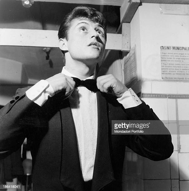 Italian singersongwriter Tony Renis tidying his bow tie at the 12th Sanremo Music Festival Sanremo 8th February 1962