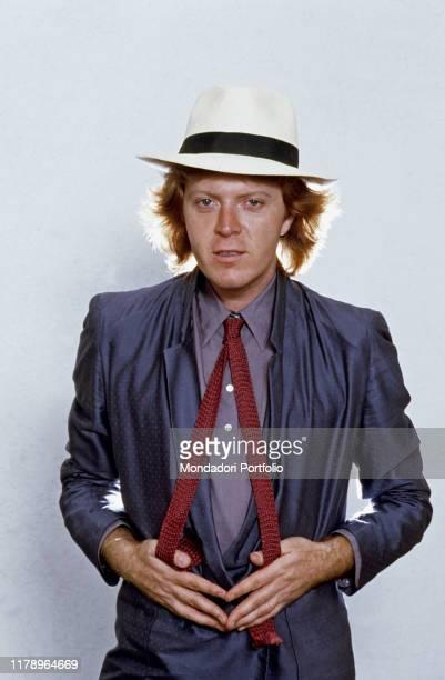 Italian singer-songwriter Umberto Tozzi strecthing apart his tie. 1979