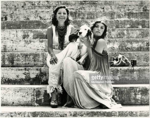 Italian sisters and singers Mia Martini and Loredana Berté sitting on some steps with a dog Rome 1970s