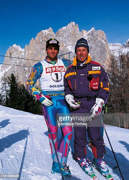 Italian skiers Alberto Tomba and Gustavo Thoeni posing on the snow wearing the ski suit 1992