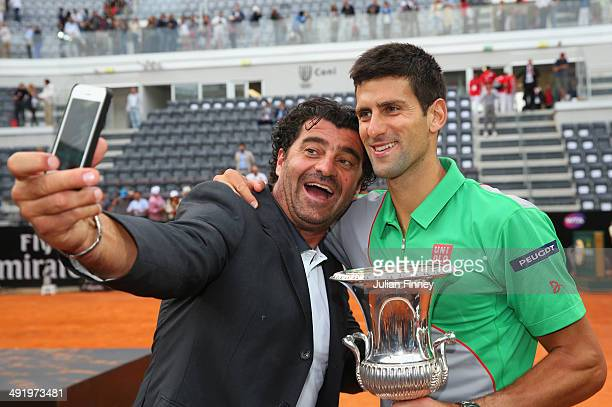 Italian skiing legend Alberto Tomba takes a selfie with Novak Djokovic of Serbia after he defeated Rafael Nadal of Spain in the final during day...