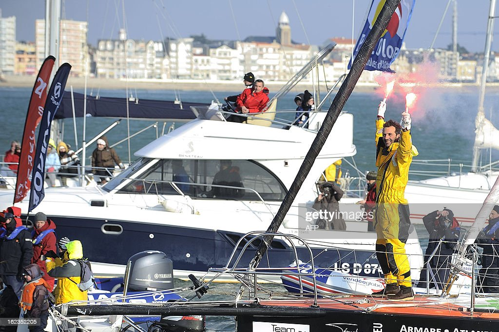 Italian skipper Alessandro di Benedetto celebrates on his monohull 'Team plastique' after crossing the finish line of the 7th Vendee Globe round-the-world solo race on February 22, 2013 in Les Sabl...