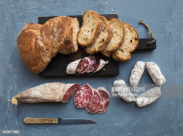 Italian slami sausages and rustic bread on dark wooden board over a rough grey-blue concrete background