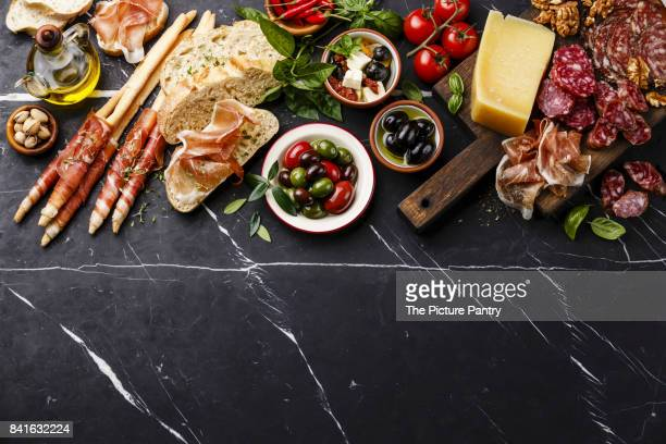 italian snacks food with ham, sliced bread ciabatta, olives, parmesan cheese, grissini bread sticks, feta cheese with dried tomatoes and sausage on dark marble background copy space - prosciutto stock photos and pictures