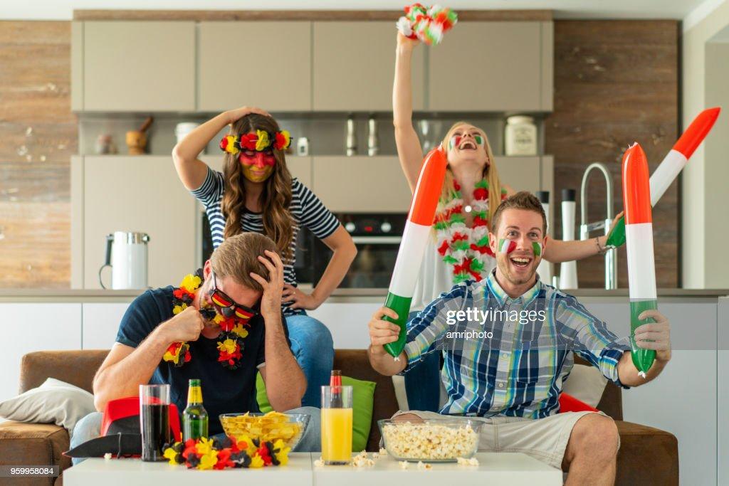 italienische Fußball Fan paar jubeln, deutschen enttäuscht vor TV-Bildschirm : Stock-Foto