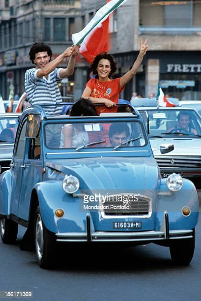 Italian soccer fans waves the Italian flag sticking out of a car's hood the Italy national football team is at the world championship's door at the...