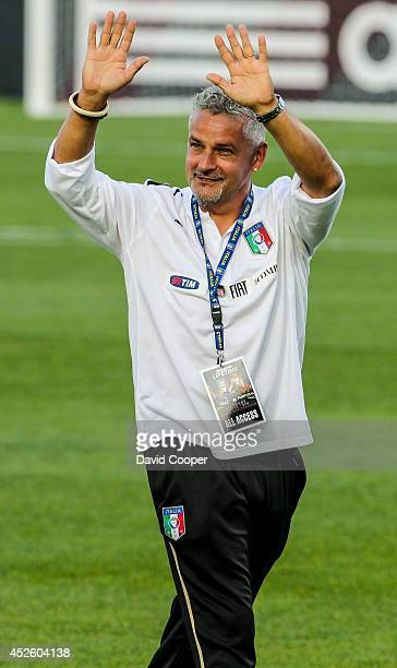 Italian soccer star Roberto Baggio waves to the crowd as the teams come onto the field for the Italy vs Portugal Legends game at BMO Field July 21...
