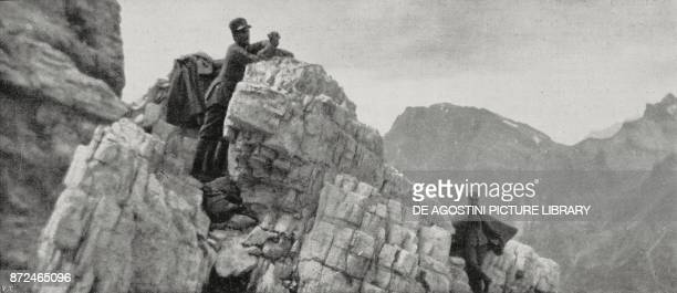 Italian soldiers clinging to the rocks to observe the moves of the enemy Alps front Italy World War I from L'Illustrazione Italiana Year XLII No 32...