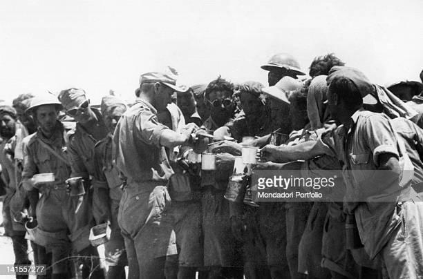 Italian soldiers distribute water to the British prisoners captured in the fortress of Tobruk Tobruk June 1942