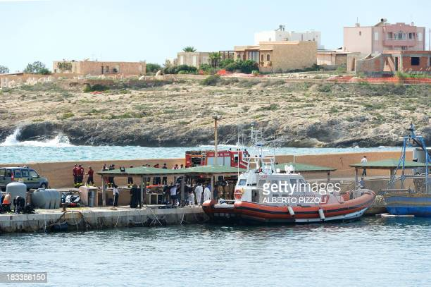 Italian soldiers firemen divers and rescuers stand by the bodies of immigrants on October 6 2013 in the Lampedusa harbour after divers recovered 10...