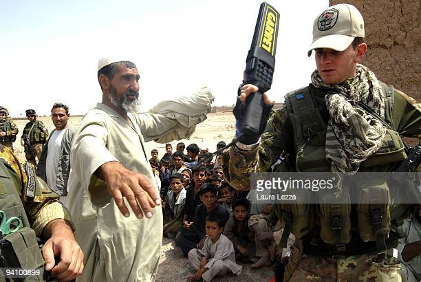 Italian soldiers of the Folgore Parachute Brigade search an Afghan man with metal detector while visiting a children school on September 16 2009 in...