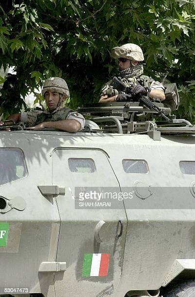 Italian soldiers of the International Security Assistance Force stand atop an armoured personnel carrier as they guard the entrance to the Italian...