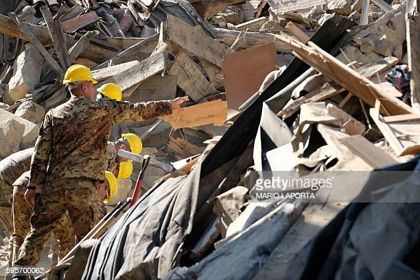 TOPSHOT Italian soldiers remove ruins during operation aiming at reopening the road in Rio a little village near Amatrice central Italy two days...