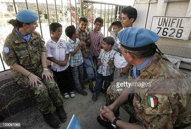 Italian soldiers serving with the United Nations Force in Lebanon talk with children from the southern Lebanese village of Yarin on July 29 during a...