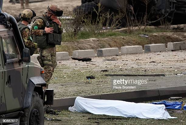 Italian soldiers stand by the body of a comrade killed after a suicide bomber hit an Italian ISAF convoy killing six soldiers while wounding four on...